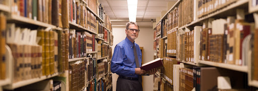 Law Library Director Scott Pagel in 2018, examining the historical materials in the Stack Level One cage.  The longest-serving director to date, Professor Pagel is the first library director with both a full professorship and a dean's title.
