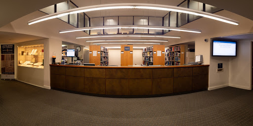 The Circulation Desk in 2018, with the rare book display case on the left, information monitor on the right, and staff and processing areas on the mezzanine above.
