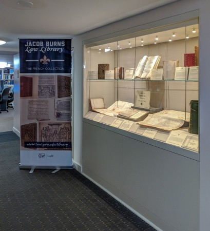PHOTO: In 2015, the purchase and installation of the archival-quality display case on the first floor was made possible by the generous donation of Robert Emery, JD 1980.  The banner celebrating the French Collection was designed by Alicia Pinkney (Information Services) in commemoration of French President Emmanuel Macron's 2018 visit to GW.
